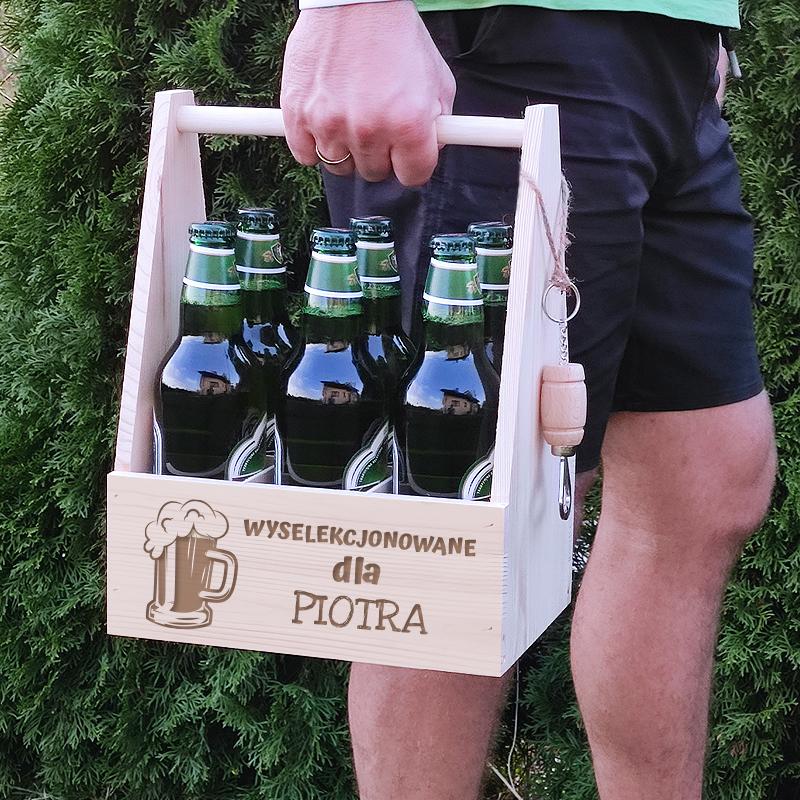 w ręku grawerowane nosidło na piwo